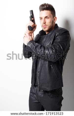 Portrait Of A Man Holding Gun against a white background not isolated.Fashion photo.