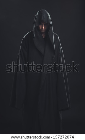 Portrait of a Man in a black robe on a dark background - stock photo