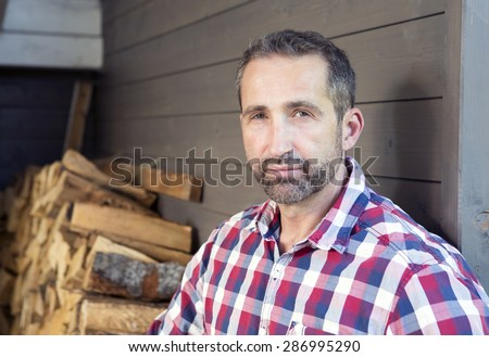 portrait of a man in a plaid shirt in front of firewood - stock photo