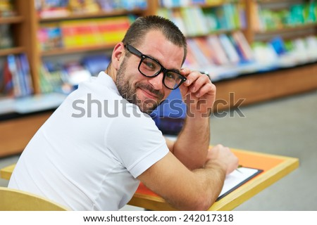 Portrait of a man in a polo shirt with glasses in a bookstore