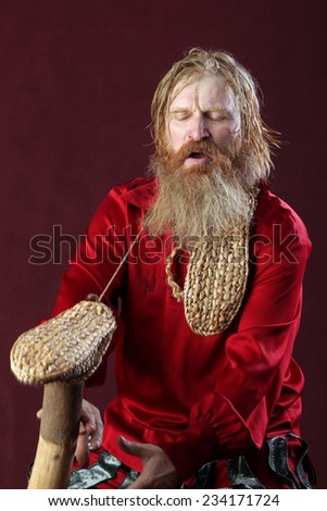 portrait of a man in a red shirt with long hair beard and mustache with a baton and bast shoes in hands studio on a burgundy background - stock photo