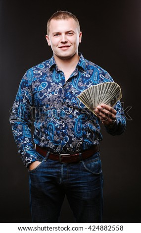 Portrait of a man in a shirt and jeans holds a lot of hundred dollar bills. The guy is holding a salary, money. - stock photo
