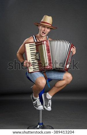 Portrait of a man in straw hat playing on accordion - stock photo