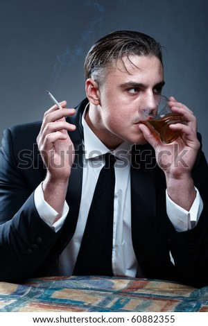 Portrait of a man in suit. Drinking whiskey and smoking cigarette - stock photo