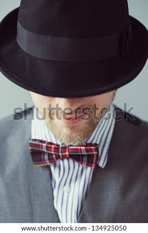 Portrait of a man in the black hat with bowtie - stock photo