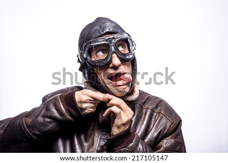 Portrait of a man in the pilot gear, clothing goggles, sticking his tongue out. Looking up.