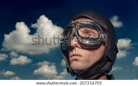 Portrait of a man in the pilot helmet & glasses on the sky background