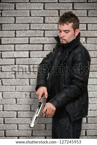 Portrait Of A Man Loading Gun against a brick wall
