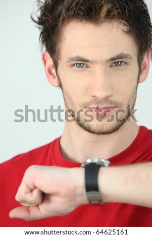 Portrait of a man looking at his watch - stock photo