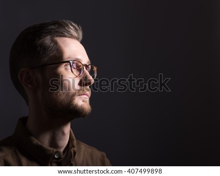Portrait of a man looking at the light from the darkness. Neutral facial expression