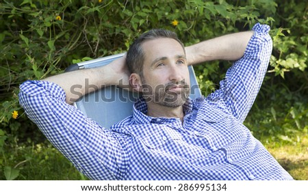 portrait of a man lying on a chair in a garden