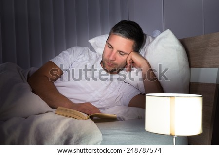 Portrait Of A Man Lying On Bed Reading Book - stock photo
