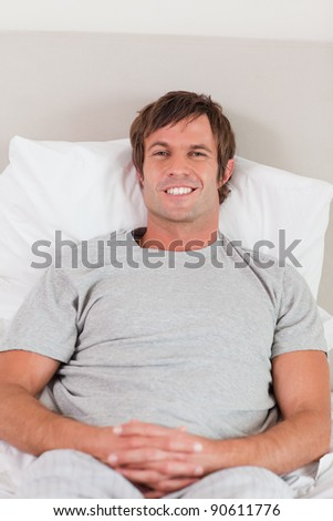 Portrait of a man lying on his bed while looking at the camera - stock photo