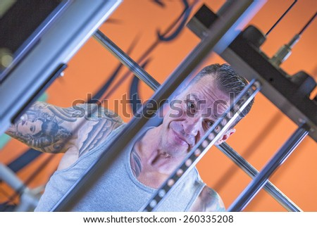 portrait of a man making behind the neck lateral pull downs - dorsal exercise - at the gym - focus on the man face