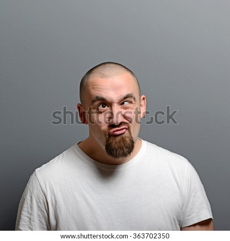 Portrait of a man making funny face against gray background - stock photo