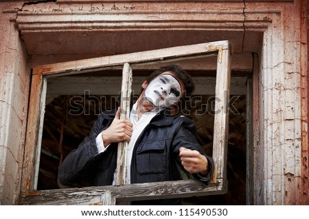 Portrait of a Man ??mime. Grimacing near the old wooden door with peeling paint