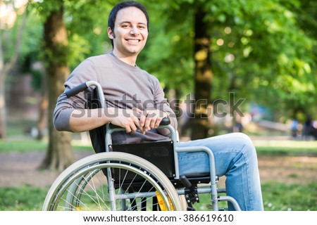 Portrait of a man on a wheelchair in a park - stock photo
