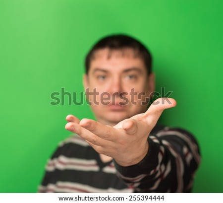 portrait of a man palm up on a green background - stock photo