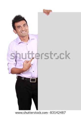 Portrait of a man peeking behind empty white billboard - stock photo