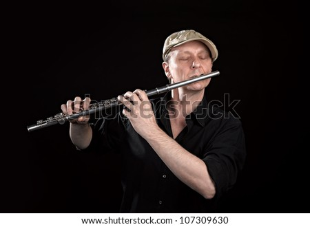 Portrait of a man playing old silver transverse flute on black background - stock photo