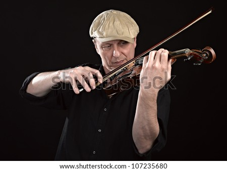 Portrait of a man playing  wooden violin on black background - stock photo