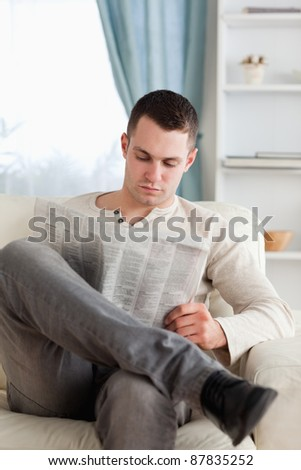Portrait of a man reading a newspaper in his living room