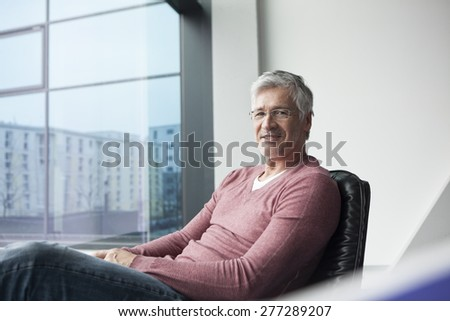 Portrait of a man relaxing in a leather chair at home