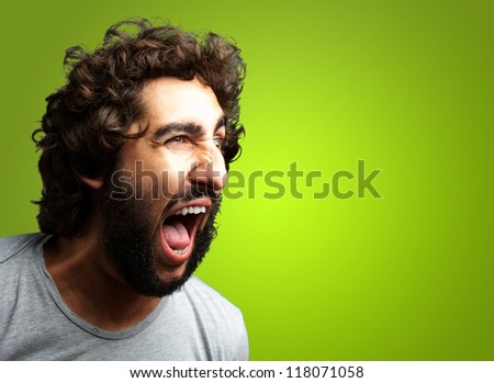 Portrait Of A Man Shouting On Green Background - stock photo