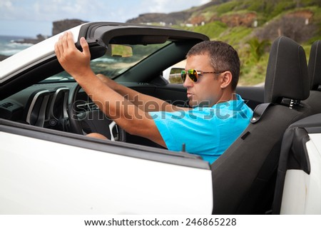 Portrait of a man sitting in his white sports car, enjoying freedom feeling happy on the Hawaiian beach, Oahu, Hawaii, USA.