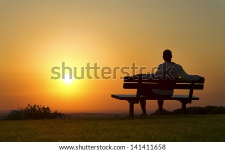 Portrait of a man sitting on a bench enjoying the Sunset - stock photo
