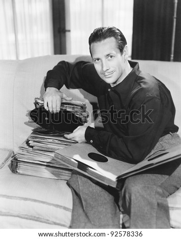 Portrait of a man sitting on a couch and taking out a record from his collection - stock photo