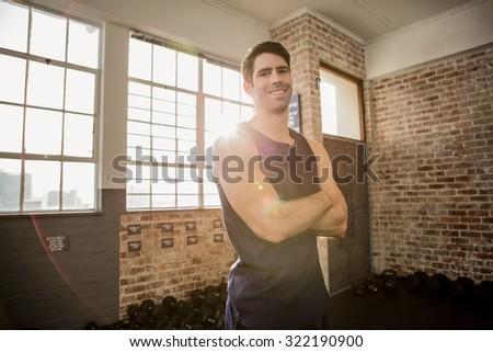 Portrait of a man smiling with arms crossed at the gym - stock photo