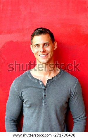 Portrait of a man standing in front of a red wall. - stock photo