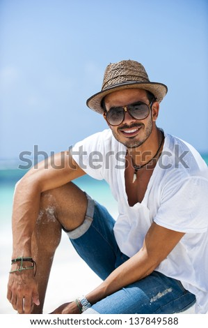 Portrait of a man staring at the camera. He is wearing a hat and casual outfit. - stock photo