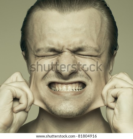 portrait of a man stretching out his cheeks - stock photo