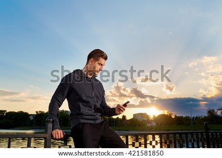 Portrait of a man takes a break from running.Talking on the phone.Jogging. - stock photo