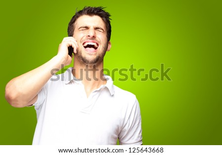 Portrait Of A Man Talking On The Cell Phone On Green Background - stock photo