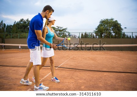 Portrait of a man training woman to play tennis outdoors - stock photo