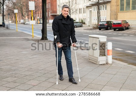 Portrait Of A Man Trying To Walk On Street With The Help Crutches - stock photo