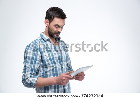 Portrait of a man using tablet computer isolated on a white background - stock photo