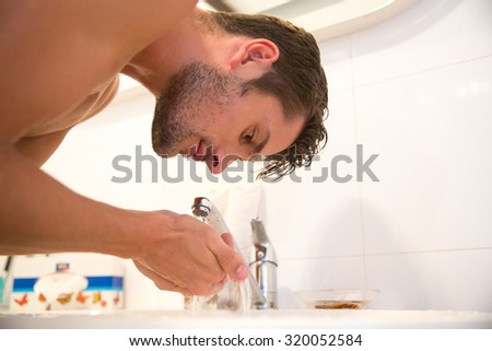 Portrait of a man washes in bathroom