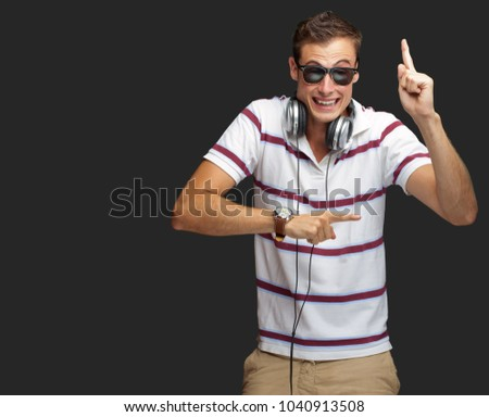 Portrait Of A Man Wearing Headphone Dancing On Grey Background