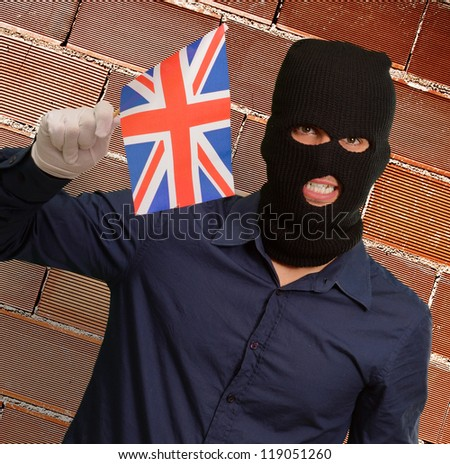 Portrait of a man wearing mask holding a flag, indoor
