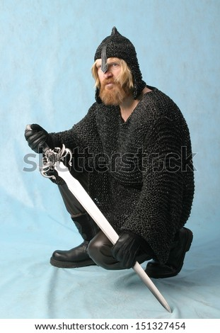 portrait of a man with a beard and mustache, a soldier in chain mail and a helmet with a sword on a light background crouched - stock photo
