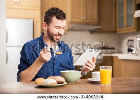 Portrait of a man with a beard watching a TV show on a tablet computer while enjoying a delicious breakfast at home - stock photo