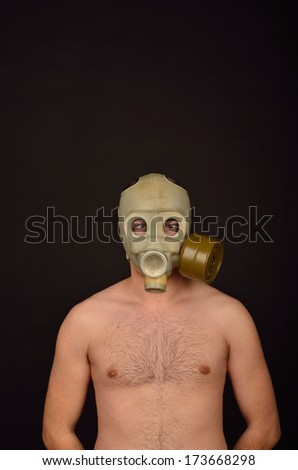 Portrait of a Man with a Gas Mask on Black Background - stock photo