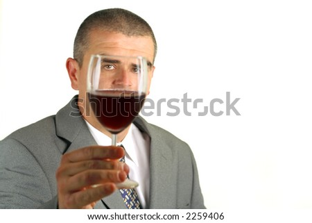 Portrait of a man with a glass of red wine in front of his face with lights reflections on the glass and eyes.Selective focus on the eye through the glass...:) - stock photo