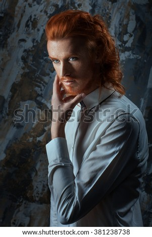 Portrait of a man with fiery curls on his head on the face of freckles. - stock photo