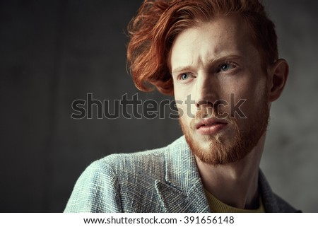 Portrait of a man with fiery curls on his head on the face of freckles.