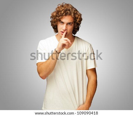 Portrait Of A Man With Finger On Lips Isolated On Grey Background - stock photo